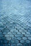 Fußwegoberfläche gebildet von den grauen sechseckigen Steinen Stockfoto