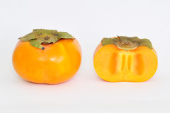 Fuyu Persimmon. A whole Fuyu Persimmon (Diospyros Kaki) and a sliced one Royalty Free Stock Photography