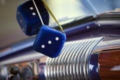 Fuzzy Blue Dice. Blue fuzzy dice hanging from a vintage car's mirror stock photography