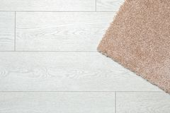 Fuzzy carpet on wooden background, top view. With space for text stock photos