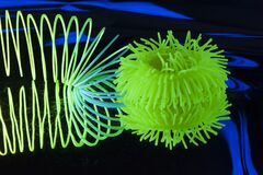 Fuzzy and circular objects are lit with fluorescent colors against a deep blue background.