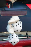 Fuzzy Dice & Baby shoes. A pair of white fuzzy dice and baby shoes hang from the rear view mirror of a classic car Royalty Free Stock Image