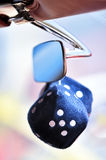 Fuzzy Dice on Rear View Mirror. Blue fuzzy dice hanging from a rear view mirror of a car Royalty Free Stock Photos