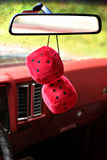 Fuzzy Mirror Dice. Fuzzy red dice hanging on the rearview mirror of a '69 Monte Carlo Stock Photography