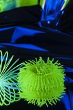 Fuzzy objects in close-up view are lit with fluorescent colors against a deep blue background.