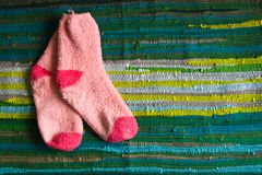 Fuzzy Pink Socks on Rag Rug Royalty Free Stock Image
