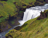 Fuzzy waterfall in green grass and mossed stones Stock Images