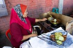 fying甜食物的妇女在亚庇 免版税库存图片