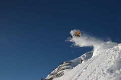 Fyling high. A snowboarder flying high in front of the blue sky Royalty Free Stock Photos