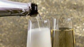 Fyllande flöjter av champagne med guld- bubblor mot guld- bokehbakgrund, begrepp av det lyckliga nya året för guld- lyxig ferie lager videofilmer