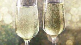 Fyllande flöjter av champagne med guld- bubblor mot guld- bokehbakgrund, begrepp av det lyckliga nya året för guld- lyxig ferie stock video