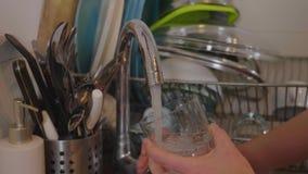 Fyllande klart vatten från en vattenkran in i ett exponeringsglas stock video