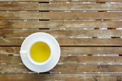 Fylld kopp te på en keramisk maträtt på trätabellen Arkivbilder