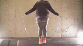 Fyllig flicka som utarbetar i idrottshall- och banhoppningrepet, viktförlust, kondition stock video