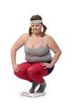 Fyllig kvinna som squatting på den svek scalen fotografering för bildbyråer