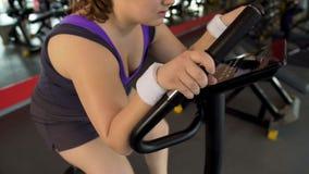 Fylligt kvinnligt funktionsdugligt hårt på den stationära cykeln i sportklubban, kroppkondition arkivbild