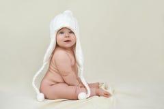 Fylligt naket tillfredsställt barn i en vit hatt royaltyfri fotografi