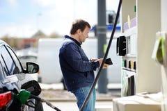 Fyllnads- bensinbränsle för man i bil arkivbilder