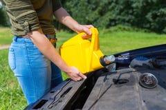 Fyllnads- bilmotor för kvinna med olja i bensindunk royaltyfri fotografi