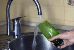 Fyllnads- exponeringsglas av vatten från den rostfria metallkökvattenkranen fotografering för bildbyråer