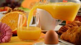 Fyllnads- exponeringsglas med orange fruktsaft på tabellen med frukosten lager videofilmer