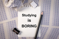 Fyllnads- ut i svarsark, blyertspenna, vässare, pappers- förminskning och studera för ord borrar Fotografering för Bildbyråer