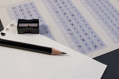 Fyllnads- ut i svarsark med blyertspenna-, vässare- och pappersförminskning Royaltyfri Bild