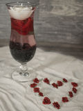 Fyllt exponeringsglas i sanden med en hjärta av rosor Arkivbilder
