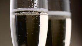 Fyllt med två exponeringsglas av champagneväsande ljudet och skum av vita bubblor close upp lager videofilmer
