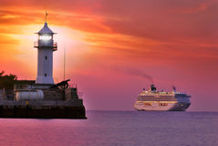 Fyr i röd skymning med skeppet Royaltyfria Foton