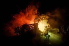 Fyr med den ljusa strålen på natten med dimma Gammalt fyranseende på berget tabell för garneringservettplatta Selektivt fokusera royaltyfria foton