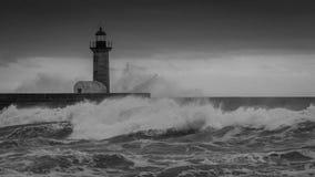 Fyr med vågor som över kraschar Royaltyfri Bild