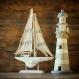 Fyr och segelbåt för gammal tappning träpå trätabellen tappning filtrerad bild nautiskt livsstilbegrepp Arkivbild