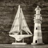 Fyr och segelbåt för gammal tappning träpå trätabellen tappning filtrerad bild nautiskt livsstilbegrepp Svart och whit arkivbilder