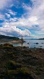Fyr och stenig kust på den södra Pender ön Arkivfoton