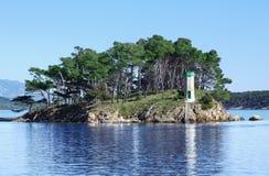Fyr på den lilla ön framme av port av den Rab staden på kroatiska seacoas royaltyfri fotografi