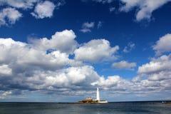Fyr på den lilla ön nära kusten Fotografering för Bildbyråer