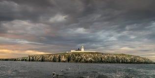 Fyr på en ö som omges av stormmoln arkivfoto
