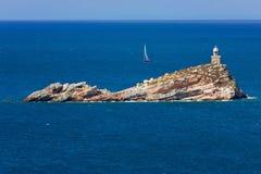 Fyr på en klippa och en segelbåt i avståndet Arkivfoton