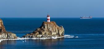 Fyr på en klippa vid havet Östligt (Japan) hav fotografering för bildbyråer