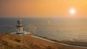 Fyr på havstranden på soluppgång Royaltyfria Bilder