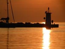 Fyr på slutet av pir av stenar, solnedgång över Adriatiskt havet, Kroatien, Europa Orange lugna hav, kontur, reflectio arkivfoton