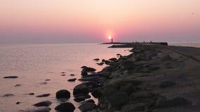 Fyr under en sista minut av solnedg?ngen med en stor sol n?stan horisonten och den klara himlen arkivfilmer