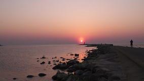 Fyr under en sista minut av solnedg?ngen med en stor sol n?stan horisonten och den klara himlen lager videofilmer