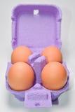 Fyra ägg i purpurfärgat förpacka Arkivfoto