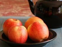 Fyra äpplen på en platta Royaltyfri Foto