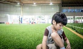 Fyra år gammal pojke är praktiserande på fotbollutbildningsfält med kopieringsutrymme royaltyfri bild