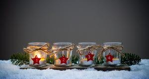 Fyra Adventstearinljus i snön Arkivbilder