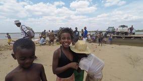 Fyra afrikanska barnungar som in camera spelar och ser i Madagscar stock video