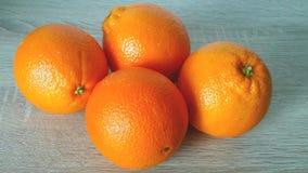 Fyra apelsiner på en träbakgrund Arkivfoton